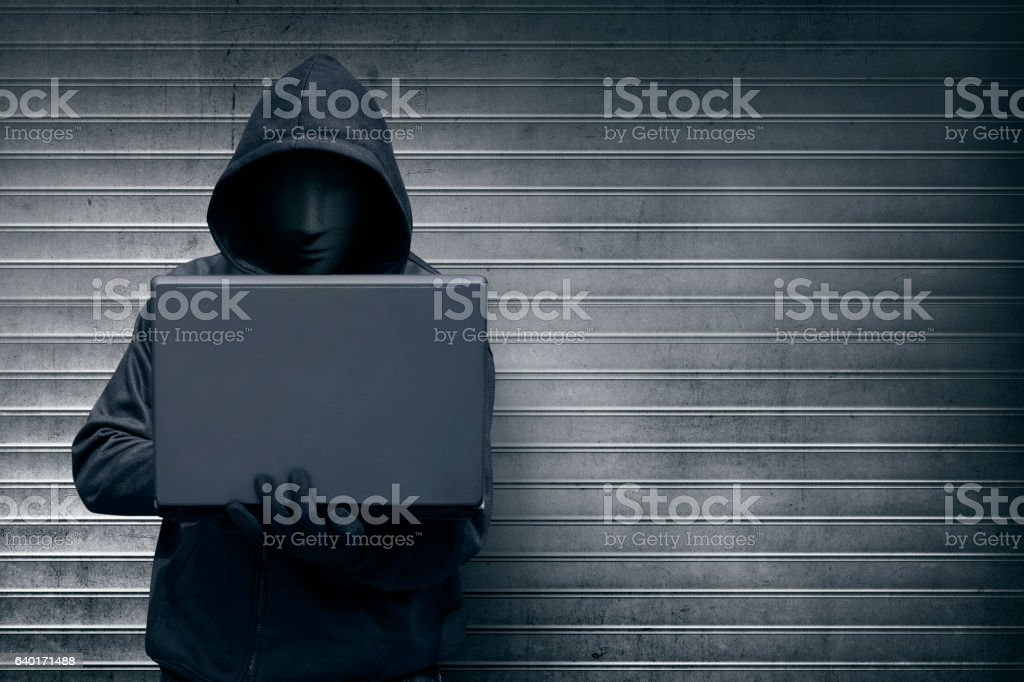 Hooded hacker with mask holding laptop while typing – Foto