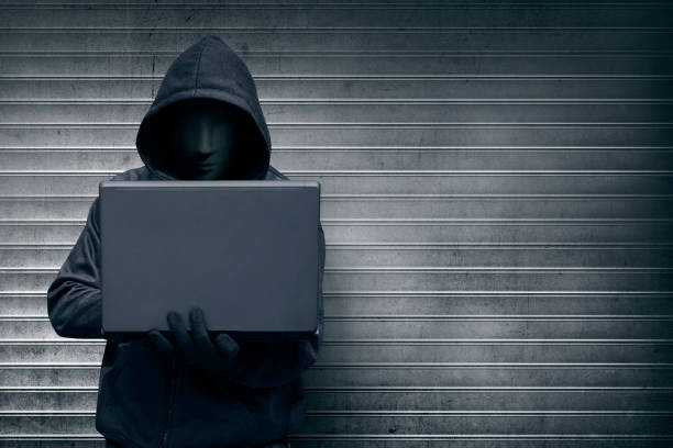 Hooded hacker with mask holding laptop while typing stock photo