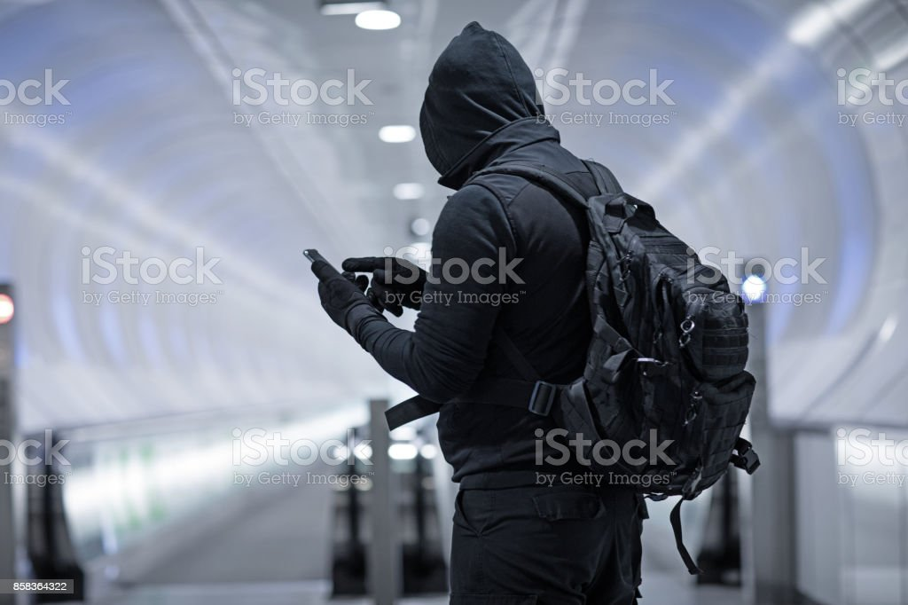 Hooded Lone wolf Man wearing black carrying bag in urban underground public transport setting stock photo