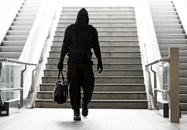 Hooded Lone wolf Man wearing black carrying bag in urban underground public transport setting Hooded Lone wolf Man wearing black carrying bag in urban underground public transport setting terrorism stock pictures, royalty-free photos & images