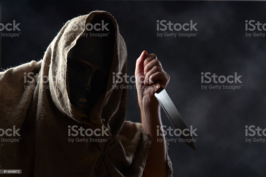 hooded man in mask with a knife - foto de acervo