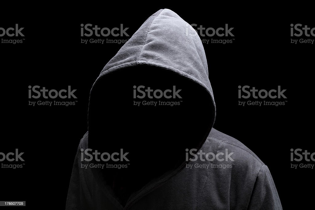 Hooded man in the shadow stock photo