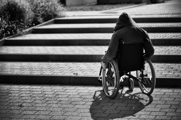 hooded man on wheelchair stock photo