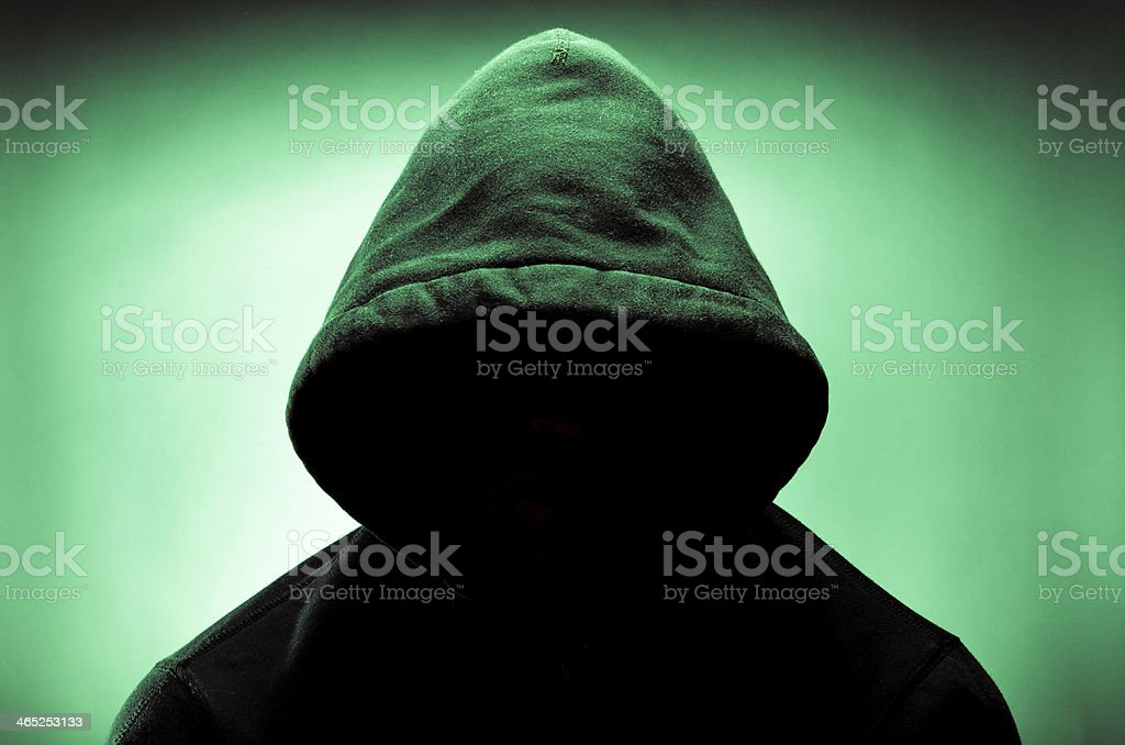 Hooded man with face in shadow stock photo