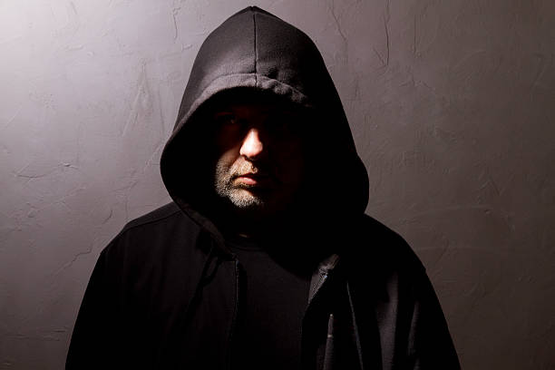 hooded man with hidden face stock photo