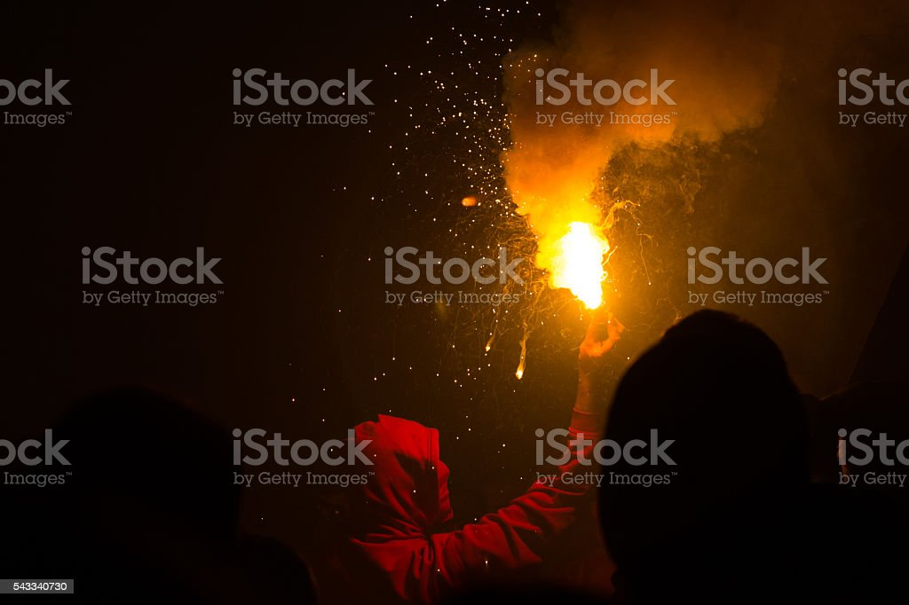 Hooded person holding torch stock photo
