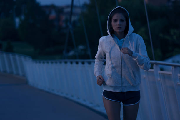 Hooded woman running in the park at night – Foto