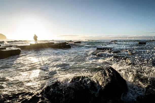 Hooded_man_silhouette_beach_morning_sun stock photo
