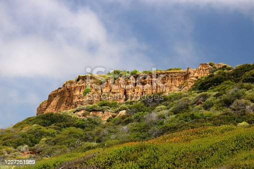 Interesting geological formation against a blue and white sky with dense green brush in the foreground.