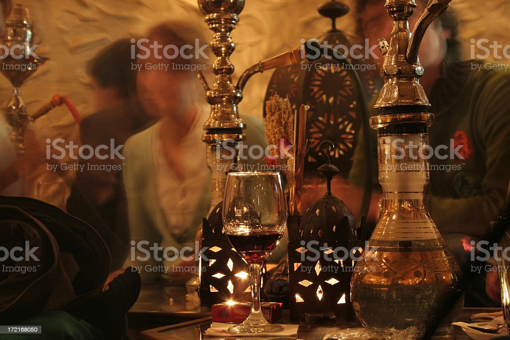 Hookah pipes next to glass of red wine and lanterns stock photo