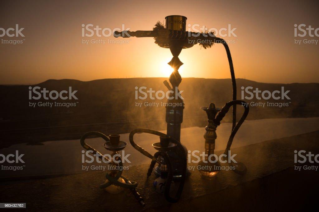 Narguilé traditionnel arabe pipe à eau, lumière de coucher de soleil directe, photo en plein air. Fond de montagne ou de Silhouettes de narguilé sur fond de coucher de soleil. En plein air. - Photo de Arabie libre de droits
