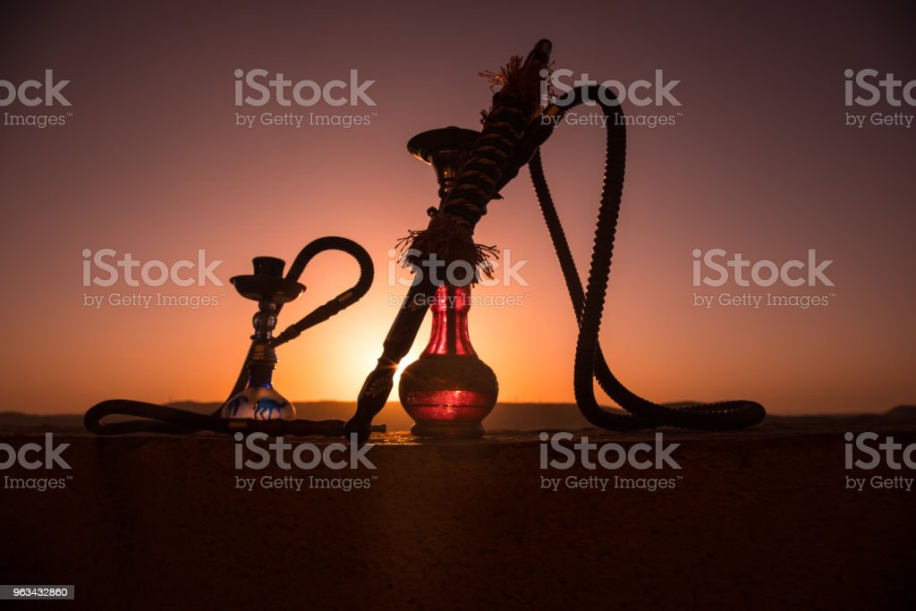 Hookah, traditional arabic waterpipe, direct sunset light, outdoor photo. Mountain background or Silhouettes of hookah on sunset background. Outdoor. - Zbiór zdjęć royalty-free (Arabia)