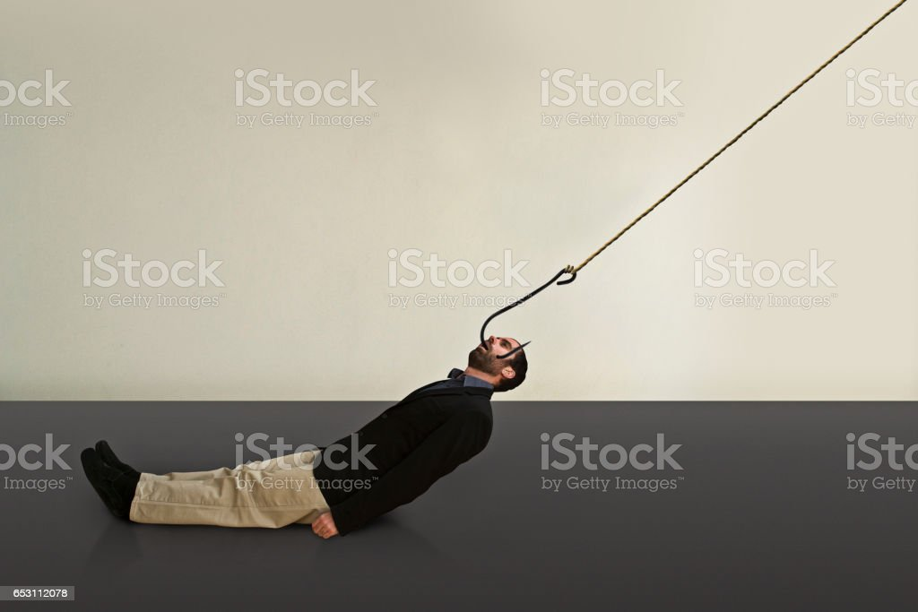 A hooked business man is dragged somewhere. stock photo