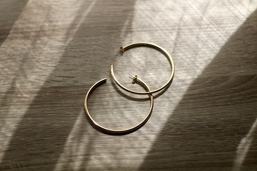 Golden hoop earrings on wooden background, illuminated by sunlight. Selective focus.