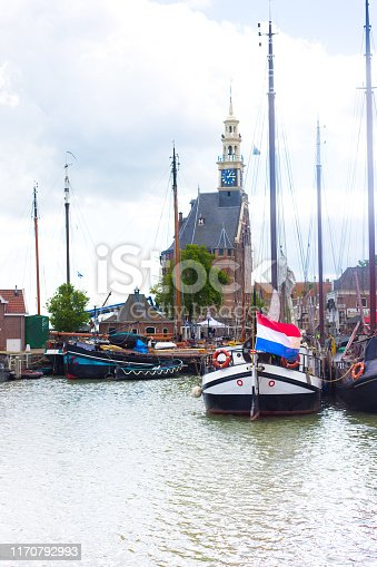 Hoorn, Holland: Vintage boats in Hoorn's harbor, with the 15th century Hoofdtoren (harbor control building) in the background. Hoorn is in province of North Holland.