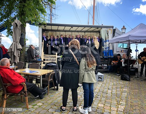 Hoorn, North Holland, Netherlands: People listening to an outdoor choir in historic Hoorn, province of North Holland.