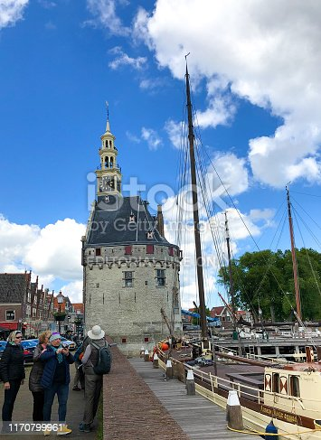 Hoorn, Holland: Tourists in the harbor of historic Hoorn, with the 15th century Hoofdtoren (harbor control building) in the background. Hoorn is in the province of North Holland.