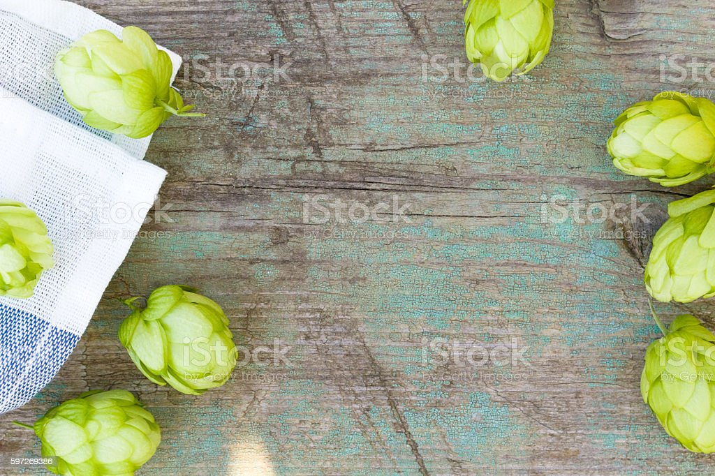 hop cones on the old wooden background, top view stock photo