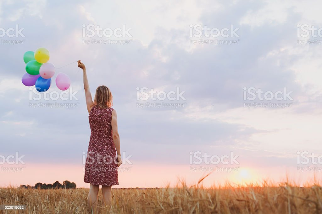 hope concept, emotions and feelings, woman with colourful balloons in...