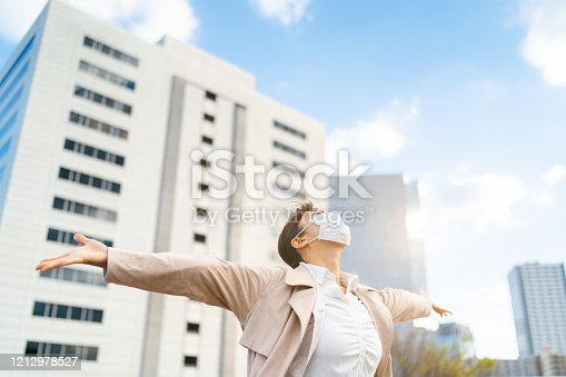 Photo of hope for a coronavirus free life concept. A businesswoman with protective facial mask is outstretching her arms while looking up