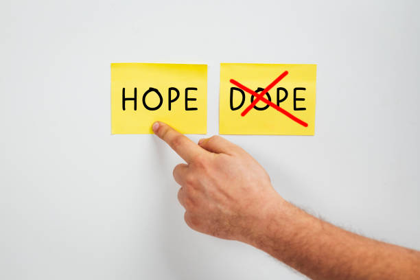Hope or Dope, Cropped man hand choose Hope - A drug abuse or drug rehabilitation concept - Say no to Dope and yes to Hope stock photo