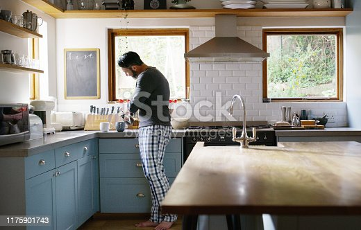 Shot of a man making two cups of coffee in the kitchen at home