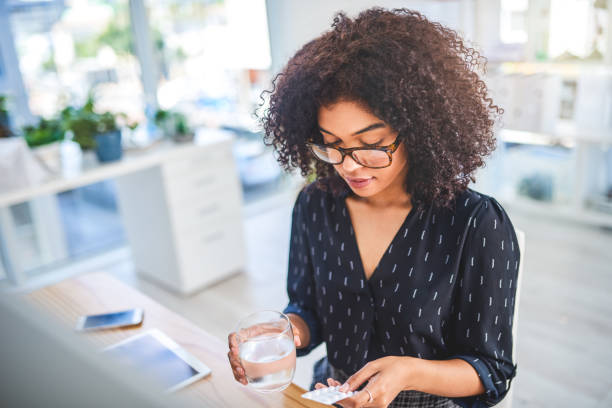 I hope these help Cropped shot of an attractive young businesswoman sitting alone in the office and taking painkillers with a glass of water woman taking pills stock pictures, royalty-free photos & images