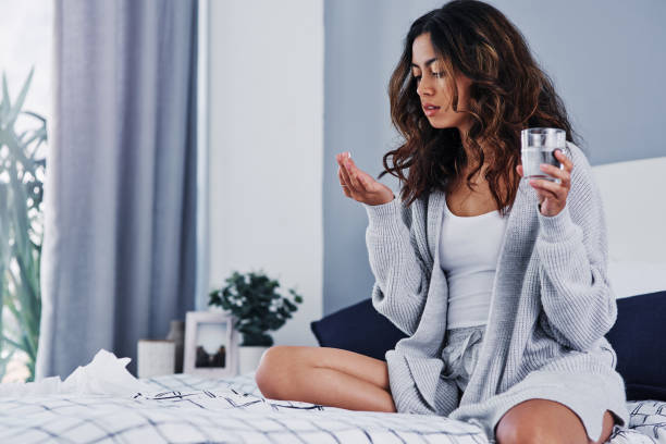 I hope this helps Cropped shot of an attractive young woman sitting on her bed at home and taking painkillers with water woman taking pills stock pictures, royalty-free photos & images