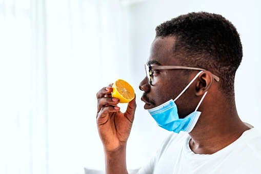 One African man Trying to Sense Smell of a Lemon at home during the day, smell blindness is one of the possible symptoms of covid-19.
