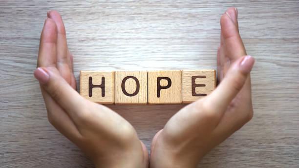 słowo nadziei wykonane przez kobiece ręce, tworzenie rodziny, oczekiwaność dziecka, szczęście - nadzieja zdjęcia i obrazy z banku zdjęć