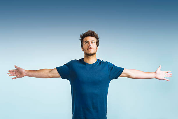 Hope: young man with arms outstretched stock photo