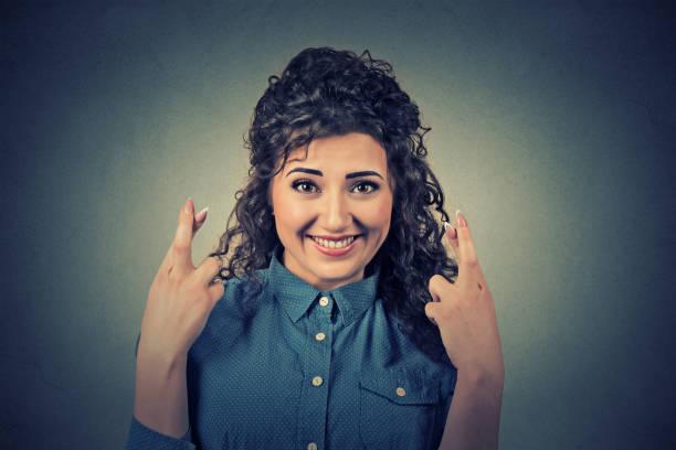 hoffnungsvolle schöne frau, die ihre finger kreuzt - zukunftswünsche stock-fotos und bilder