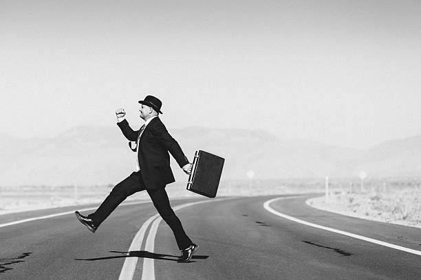 Hopeful businessman with suitcase crossing the road stock photo