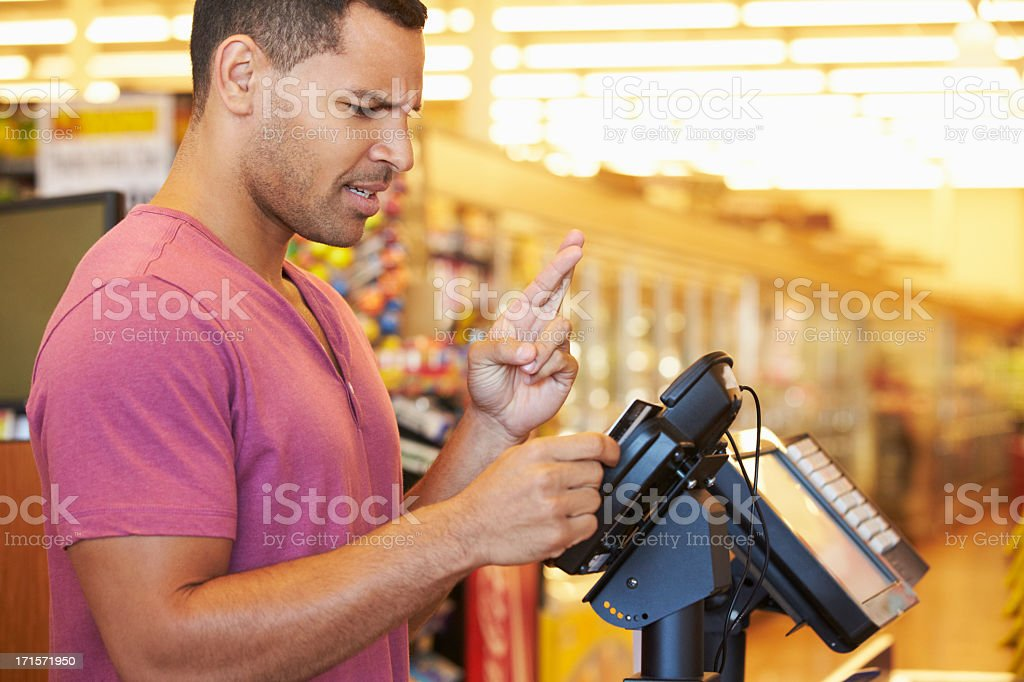 Hopeful Customer Paying For Shopping At Checkout stock photo