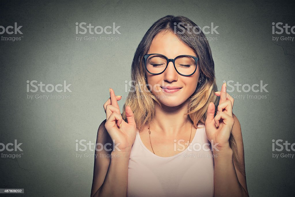 hopeful woman crossing her fingers, eyes closed stock photo
