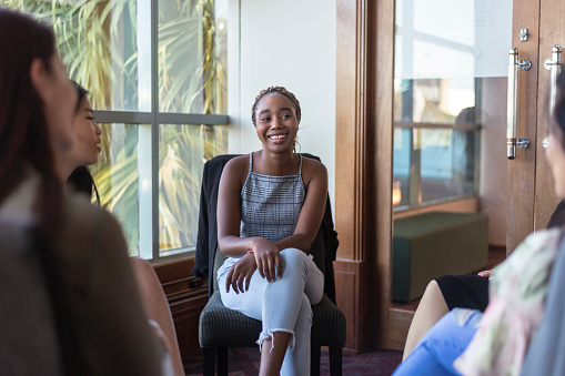 A young black woman smiles while sharing her emotions and experiences with supportive group members in a group therapy session. Vulnerability, community and mental health concepts.