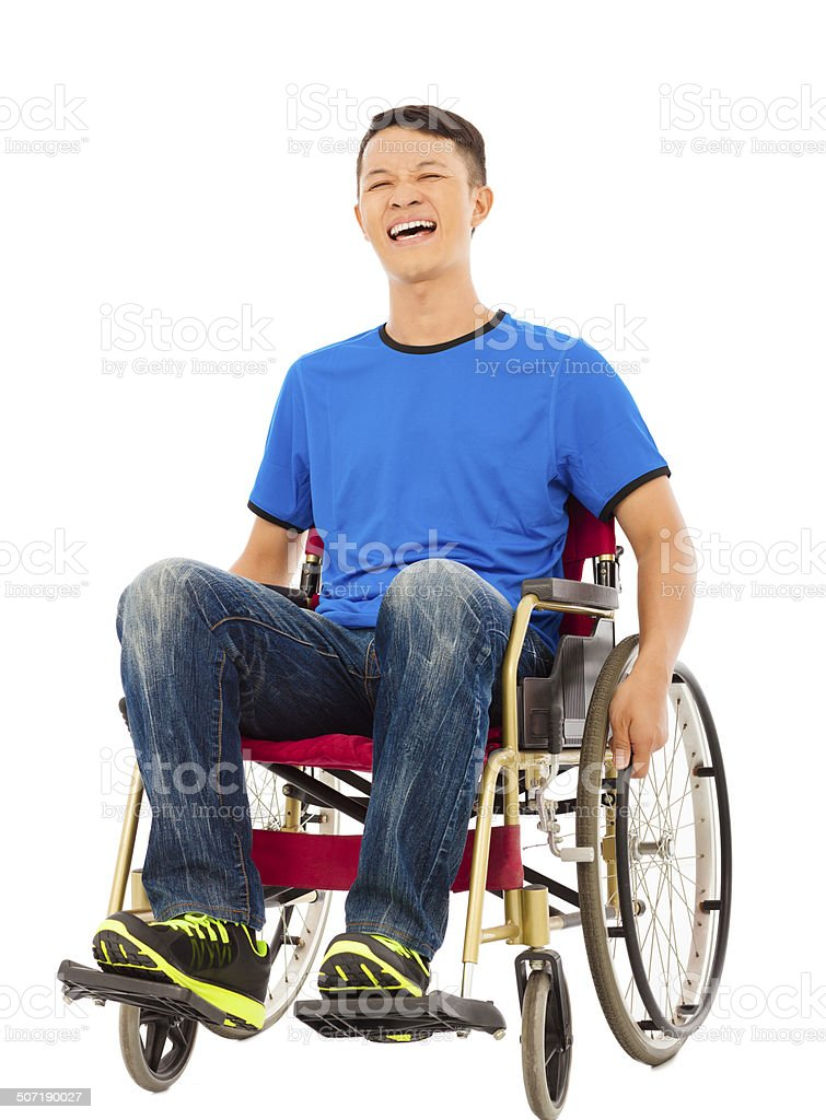hopeful young man sitting on a wheelchair in studio stock photo