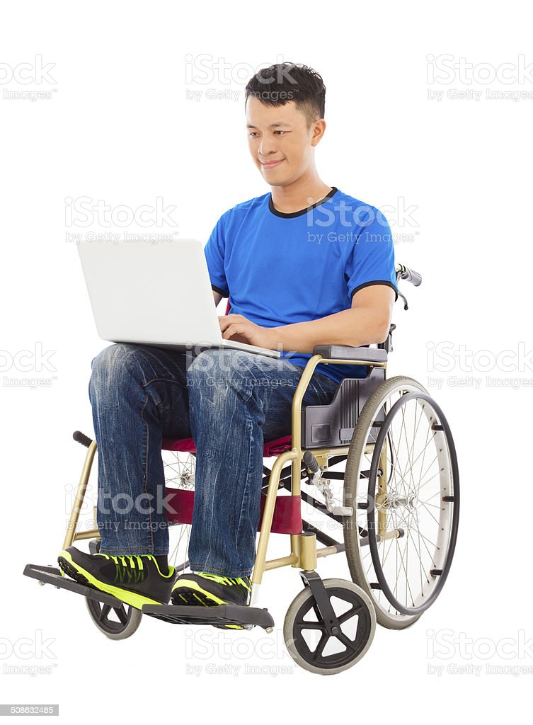 hopeful young man sitting on a wheelchair with a laptop stock photo