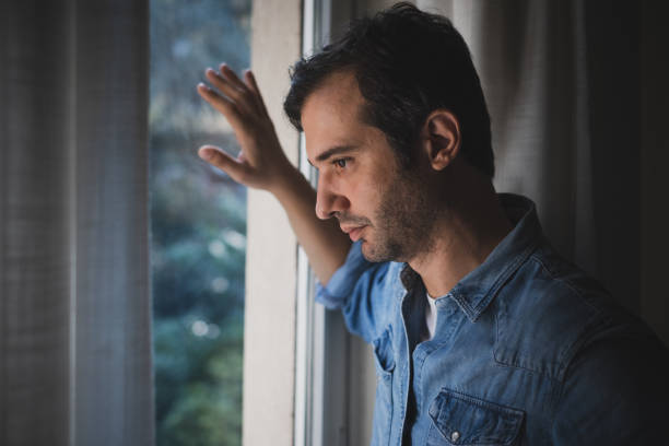 Hopeless man feeling alone and lost looking out window stock photo
