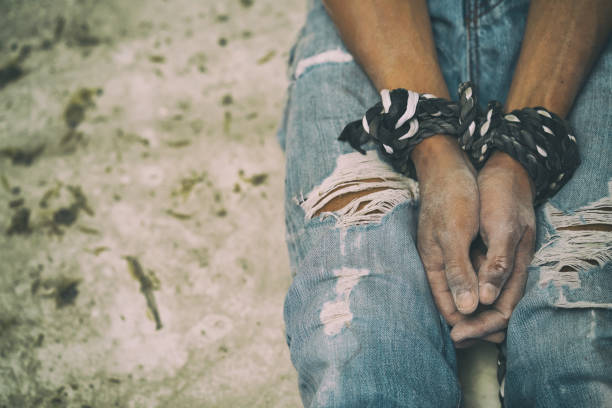 hopeless man hands tied together with rope - human trafficking stock photos and pictures