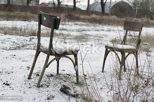 Hopelessness. Sadness. Yearning. Loneliness. Two old chairs stand in an empty field