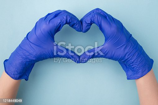 Hoping for the best concept. Top above overhead close up photo of hands gesturing heart isolated over blue color background