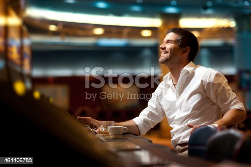 smiling handsome man hoping to win at slot machine