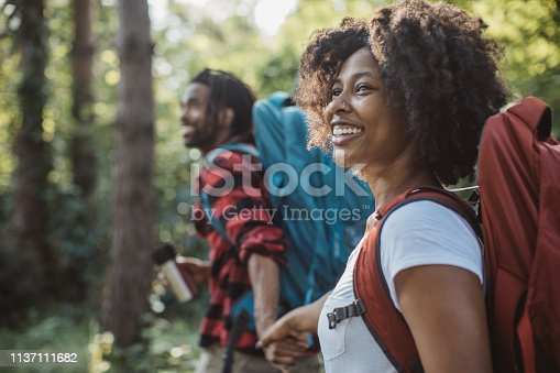 Young couple on vacation in countryside, they enjoy in summer. They walking through forest, exploring nature and drinking hot coffe from travel mug