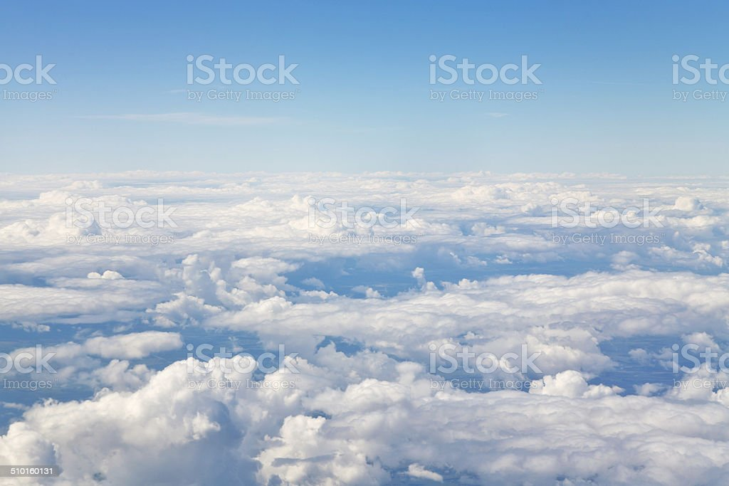 horizon above white clouds in blue sky stock photo
