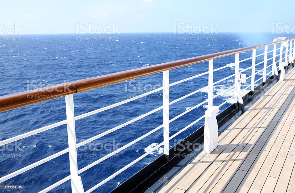 Horizon view from empty cruise ship deck on a sunny day Watching the horizon from a cruise ship deck Blue Stock Photo