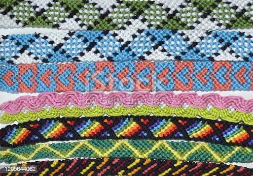 Horizontal background made of variety of colorful friendship bracelets handmade of knots