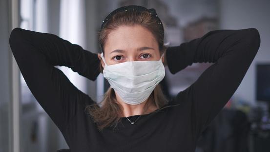 horizontal background of woman wearing surgical mask for corona virus isolation .