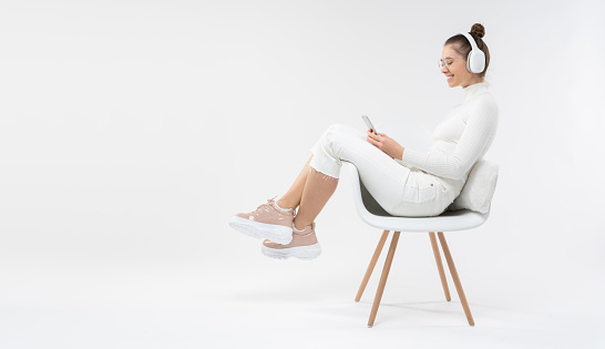 Horizontal banner of girl sitting on white chair, wearing casual clothes and trainers, listening to music in headphones, looking at phone, copy space on left, isolated on gray background