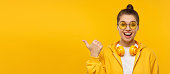 istock Horizontal banner of young excited female wearing t-shirt, hoodie, glasses and wireless headphones around neck, pointing to copy space, isolated on yellow background 1227242500